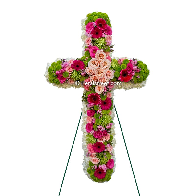 Mixed flower funeral cross with pink, magenta, and green flowers and accents.