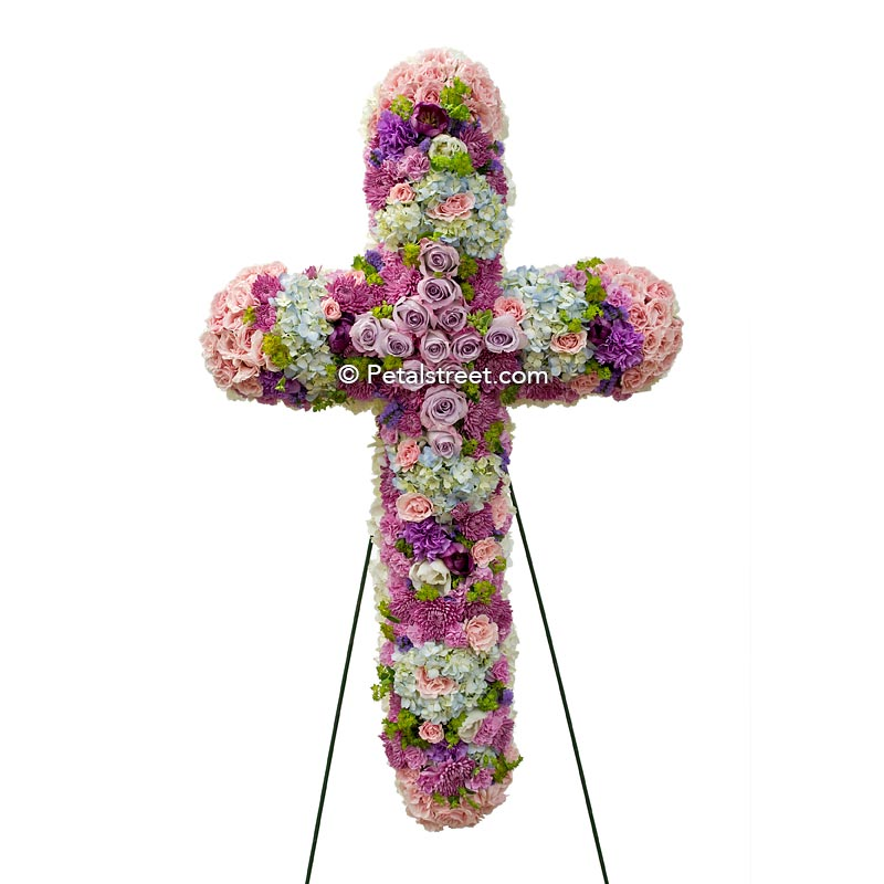 Mixed flower funeral cross with pink, lavender, and white flowers.