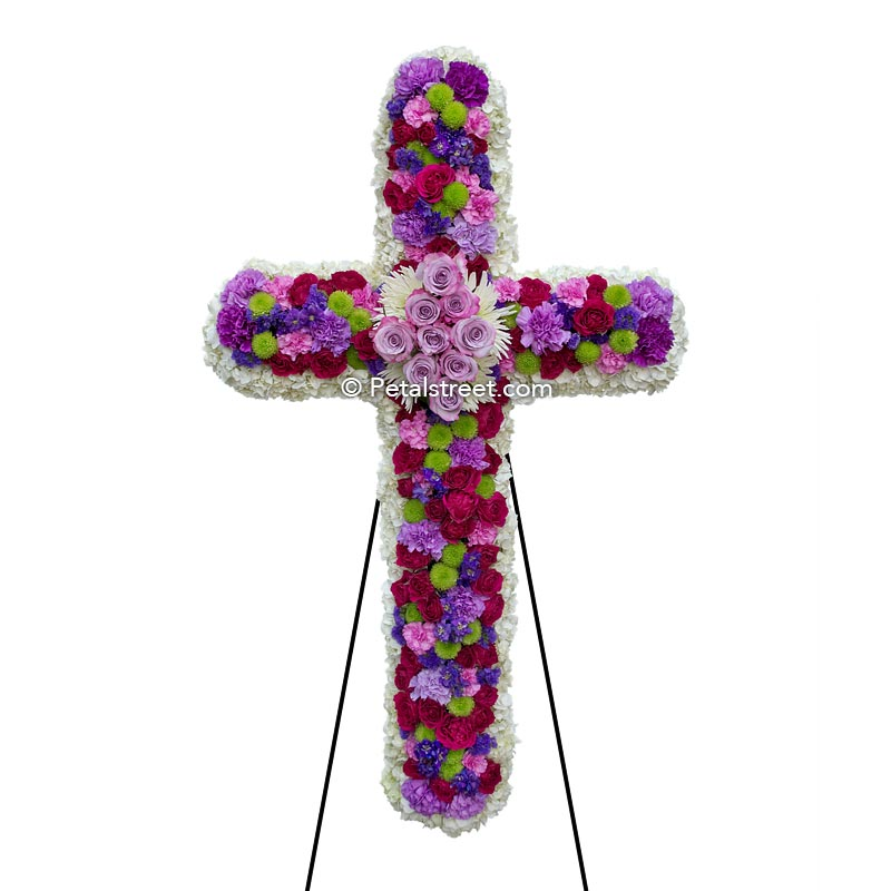 Mixed flower funeral cross with white, purple, and magenta mixed flowers.