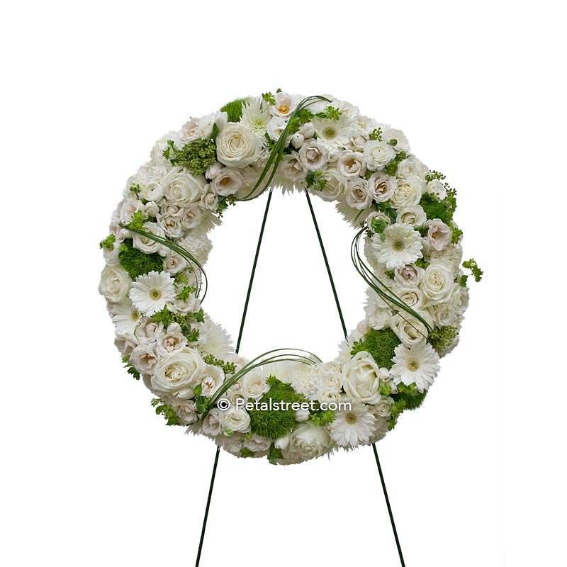 All white funeral wreath with a mix of flowers such Roses, Daisies, and Hydrangea.