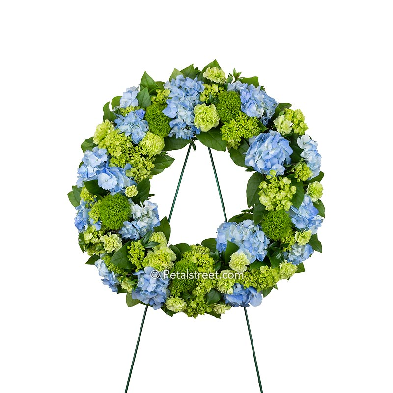 Beautiful funeral wreath with blue and green Hydrangea, Carnations, Green Trick, and mixed greenery.