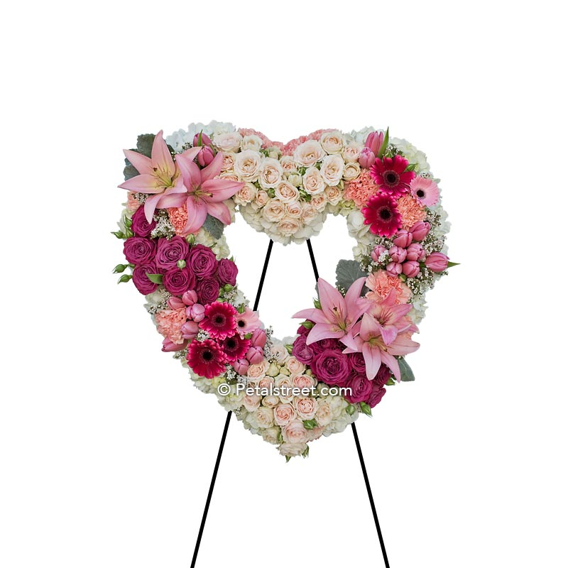 Funeral flowers heart form with pink Lilies, pink & white Roses, Carnations, Hydrangea, and accent foliage.