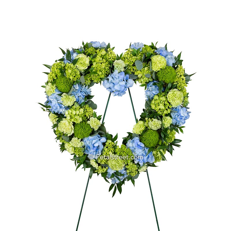 Beautiful blue and green funeral heart wreath with a mix of Hydrangea, Carnations, Green Trick, and foliage accents.