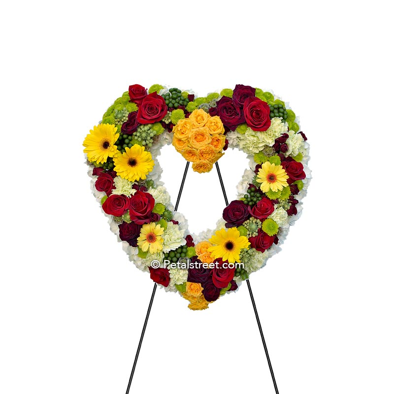 Colorful heart form with red & yellow Roses, yellow Daisies, white Hydrangea, green Button Mums, and Carnations.