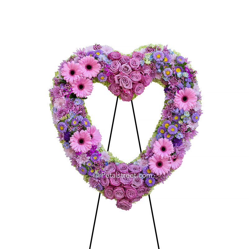 A flower abundant funeral heart form, with a variety of soft pinks and purples, includes Roses, Gerbera Daisies, large Asters, and a mix of accent flowers.