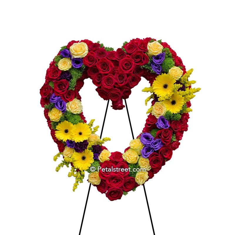 Vibrant funeral flower heart form with red Roses, yellow mini Roses, yellow Gerbera Daisies,  Solidago, and Lisianthus.