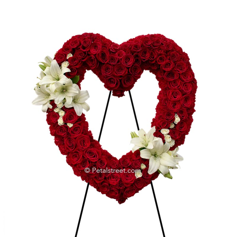 Red Rose funeral heart form with red Carnation outline and gorgeous white Lilies accenting the upper left and lower right of this piece.