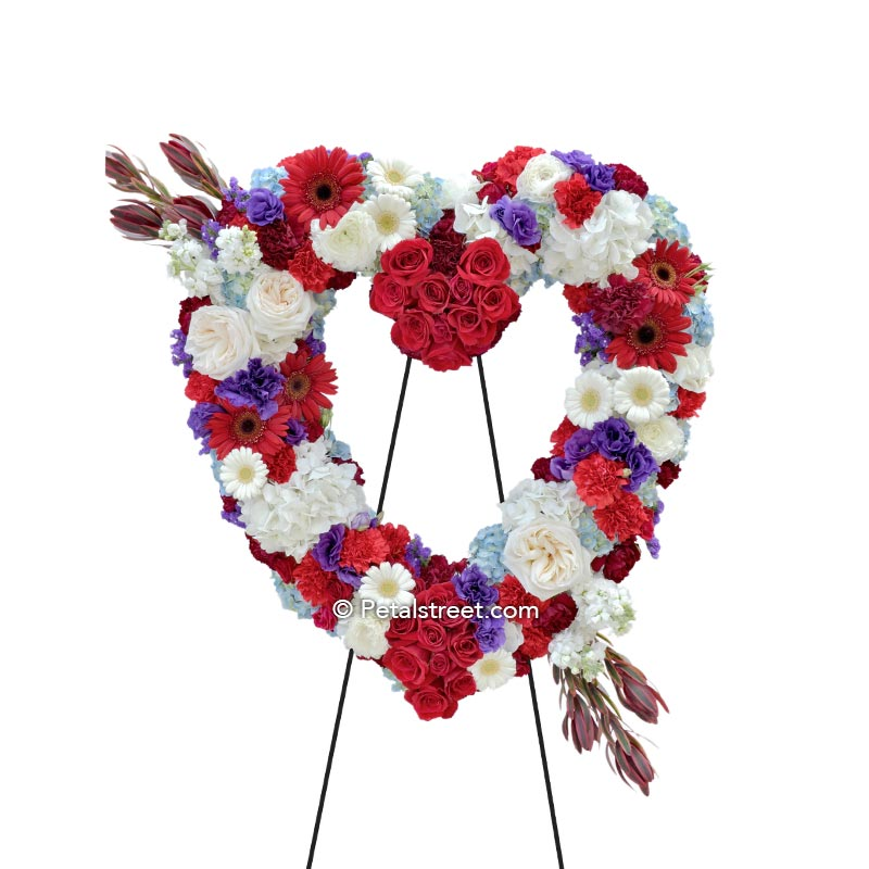 Red, white, blue funeral flower heart form with Roses, Daisies, Carnations, Hydrangea, and Lisianthus.