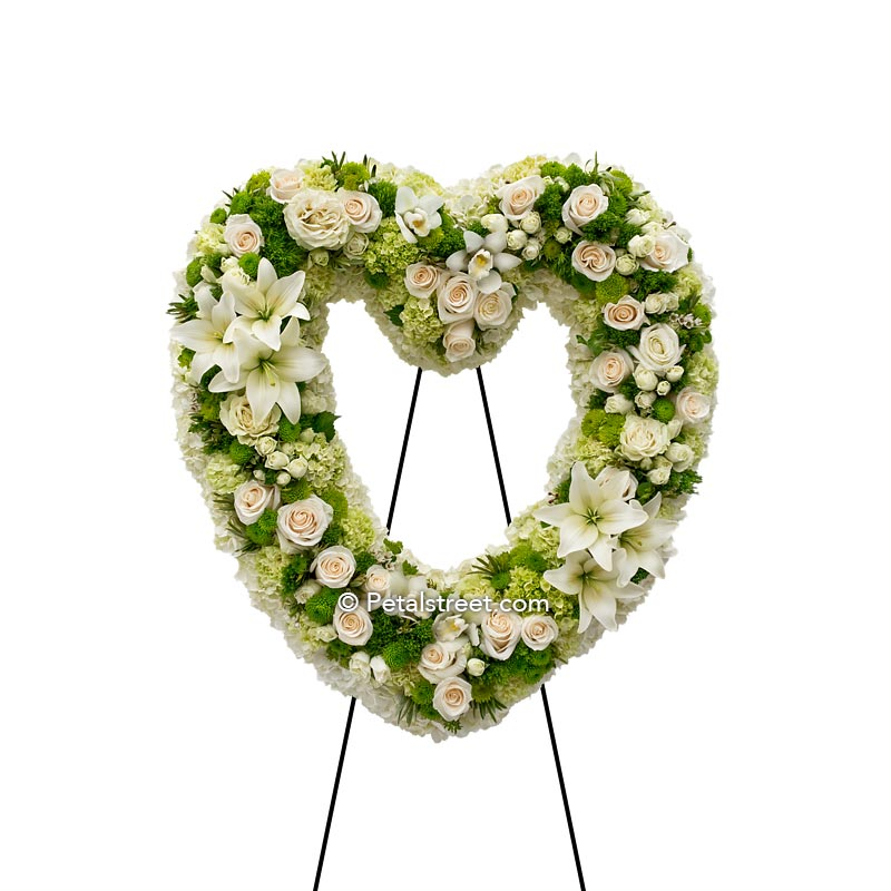 All white funeral flower heart form with Roses, Lilies, and Orchids accented with green Carnations, Green trick, and foliage touches.