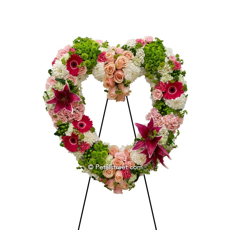 Funeral flower open heart form with pink Lilies, Roses, and Daisies accented with green Button Mums, Spider Mums, and Bupleurum.