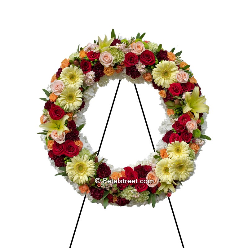 Funeral wreath with Roses, Daisies, and Carnations in bright colors.