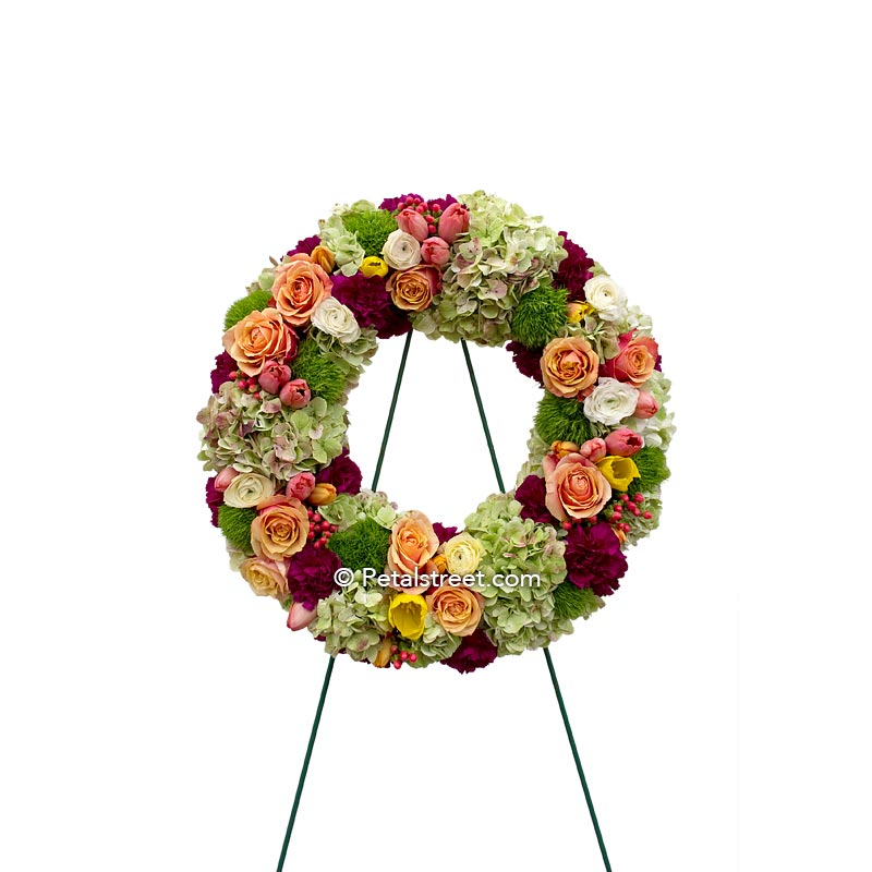 Beautiful funeral wreath in soft oranges and greens with Roses, Carnations, Hydrangea, and mixed accents.
