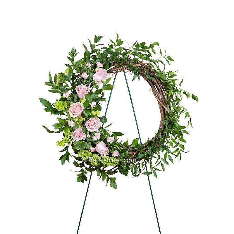 Grapevine and foliage funeral wreath with pink mini Gerbera Daisies, purple Aster, green mini Hydrangea, Snap Dragons, and Solidago.