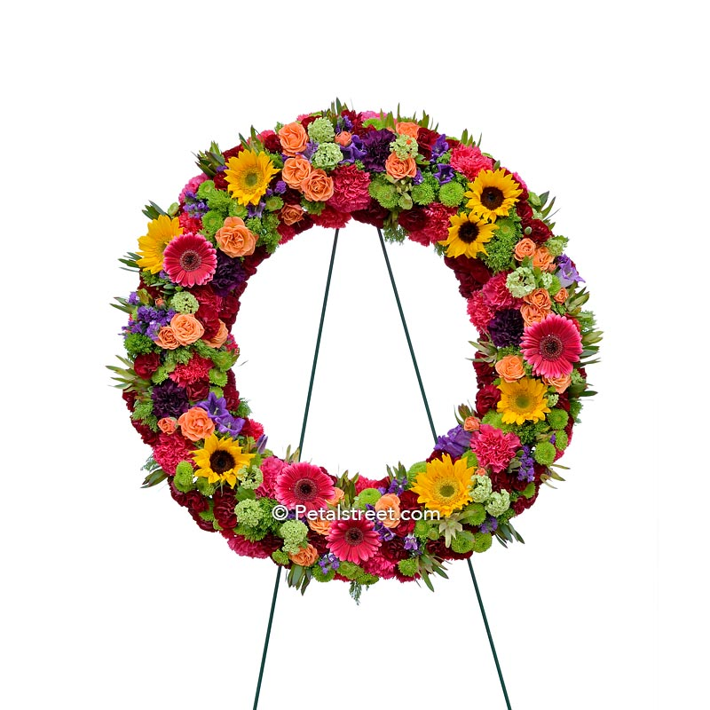 Vibrant funeral wreath with Sunflowers, Gerbera Daisies, Roses, and mixed accents.