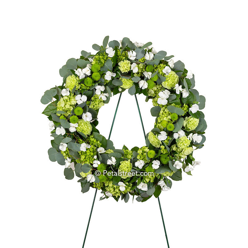 Funeral wreath with white Dianthus softly mixed among a variety of green flowers such as mini Hydrangea, Carnations, and Button Mums, as well as Eucalyptus and mixed greenery.