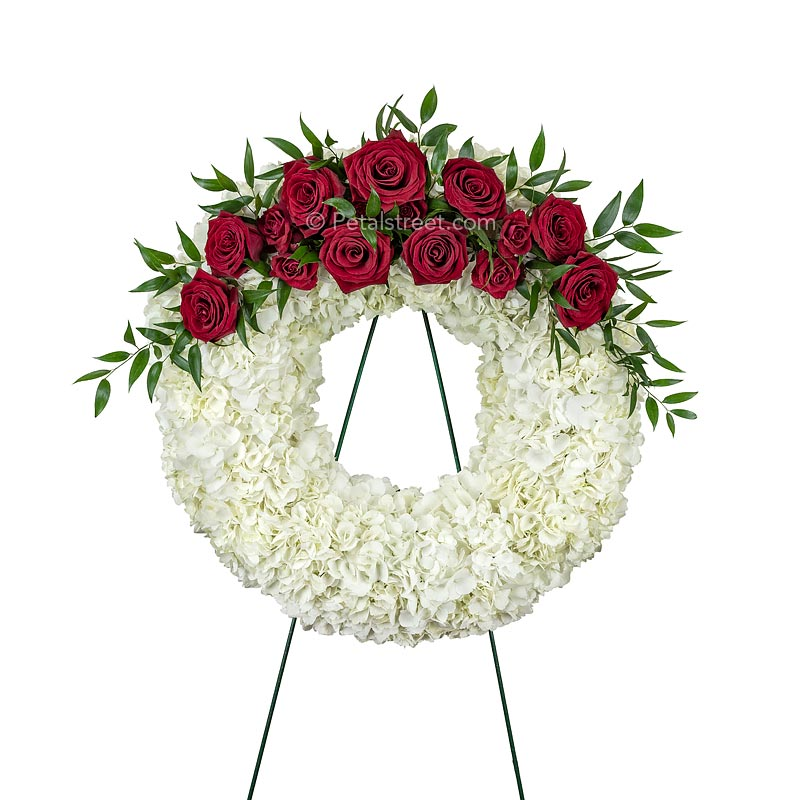 Simple and elegant, this funeral wreath is arranged with red Roses, white Hydrangea, and accent foliage.