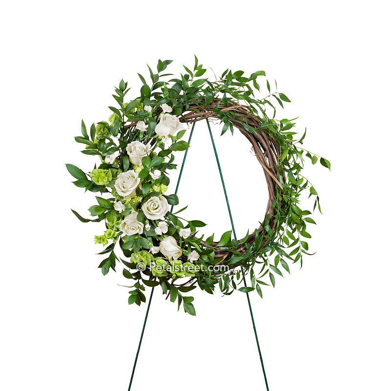 Funeral wreath made on a dried grapevine ring with white Roses, white accent flowers and mixed foliage made by Petal Street Flower Company florist in point pleasant, NJ.