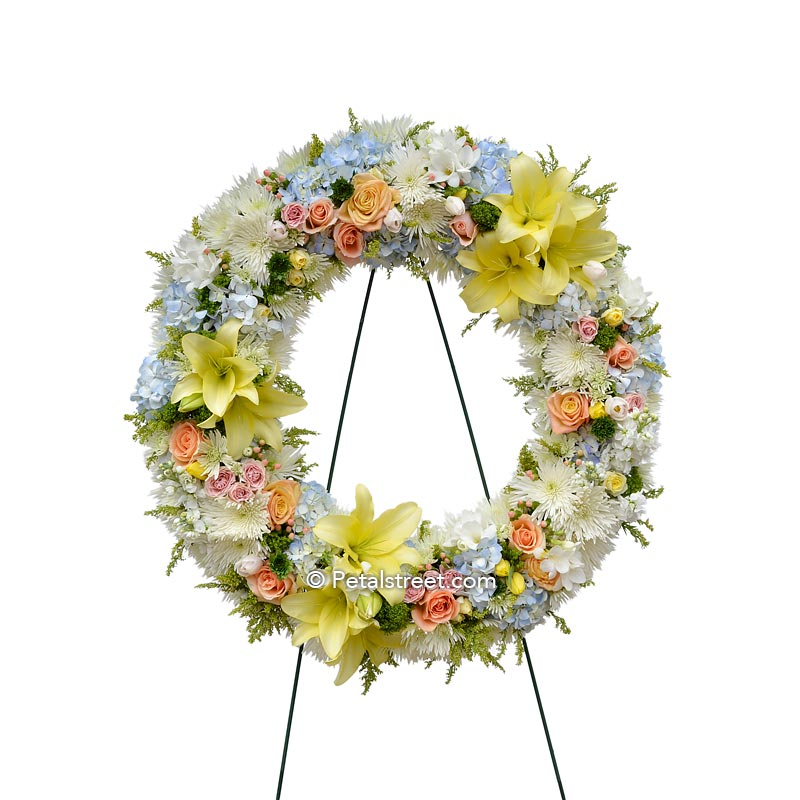 Funeral wreath with mixed flowers in soft colors such as yellow, peach, and white.