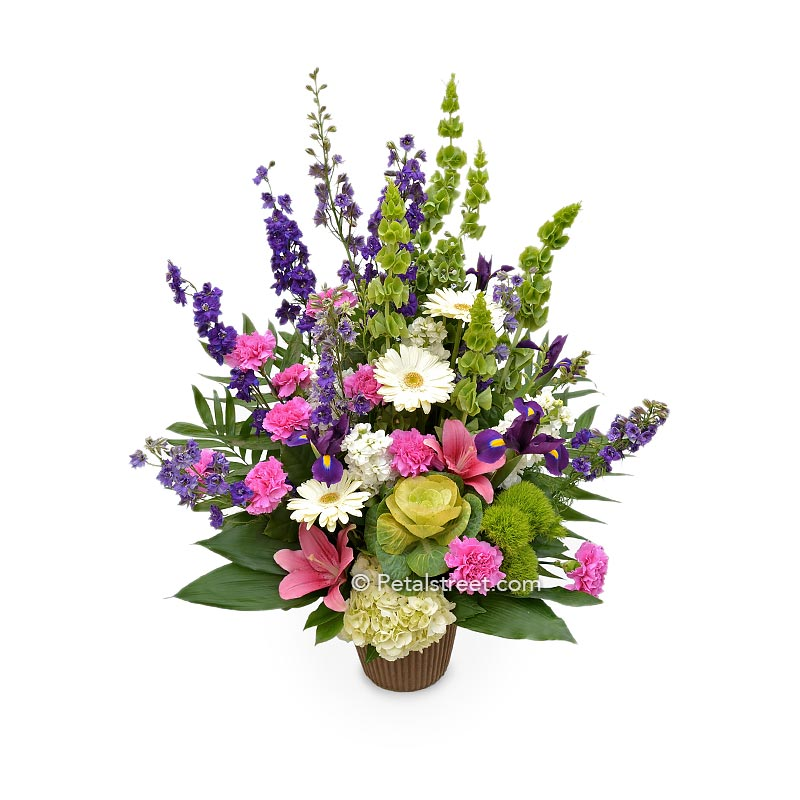 Garden style funeral basket with pink Lilies, white Daisies, Carnations, Larkspur, and Bells of Ireland.