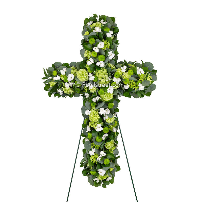 A beautiful funeral cross and an excellent Irish funeral cross with green and white flowers and lush accent foliage.