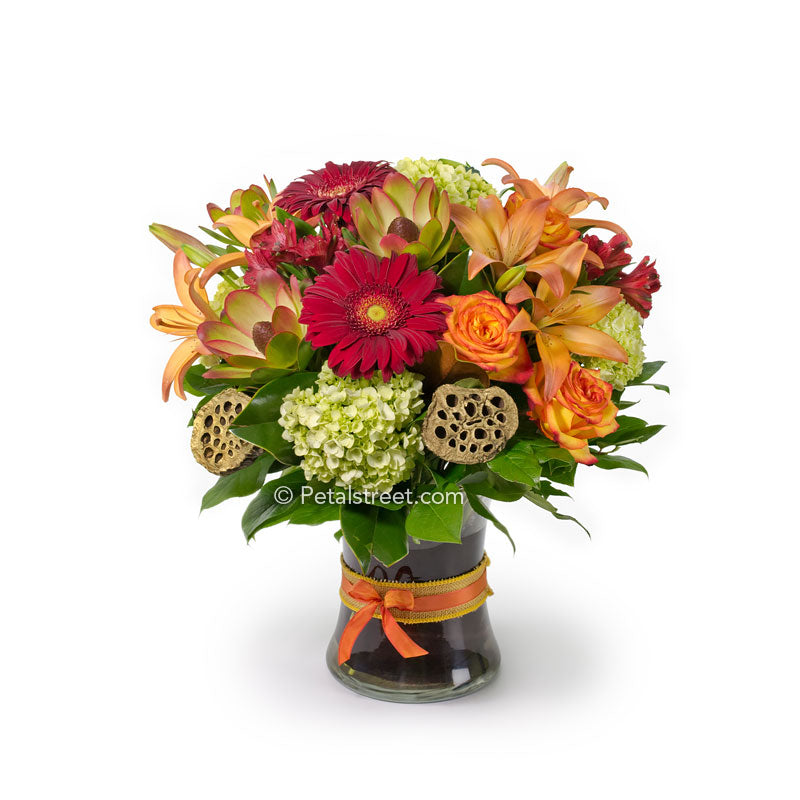 Orange Roses, red Gerbera Daisies, orange Lilies, green Hydrangea, Lotus Pods, red Alstroemeria, and foliage accents arranged in a large vase.