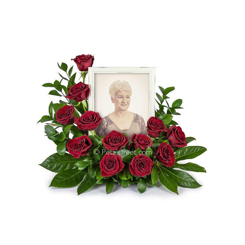 Cremation memorial floral arrangement with red Roses surrounding a photo frame of a loved one