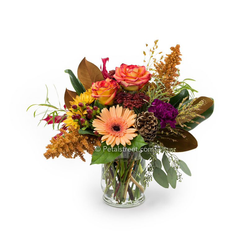 Orange Roses, Gerbera Daisies, Mums, red Berries, and Pine Cone Accents arranged in a vase.