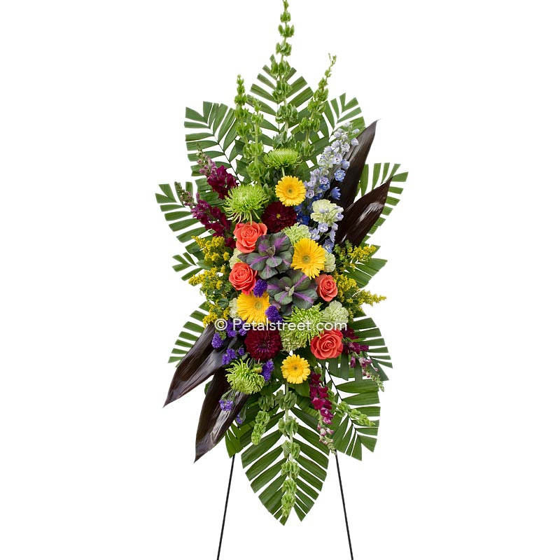 This standing spray has yellow Daisies and orange Roses accented with a colorful assortment of complimentary flowers.
