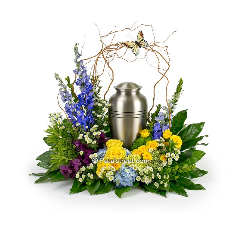 Cremation urn flower arrangement with yellow Roses, blue Delphinium, plum Orchids, decorative Curly Willow arch with a butterfly accent.