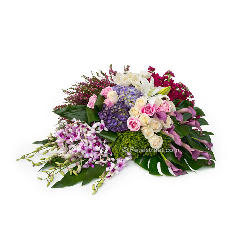 Gorgeous family casket spray with pink and white Roses, Hydrangea, Orchids, plum Calla Lilies, and lush tropical leaves.
