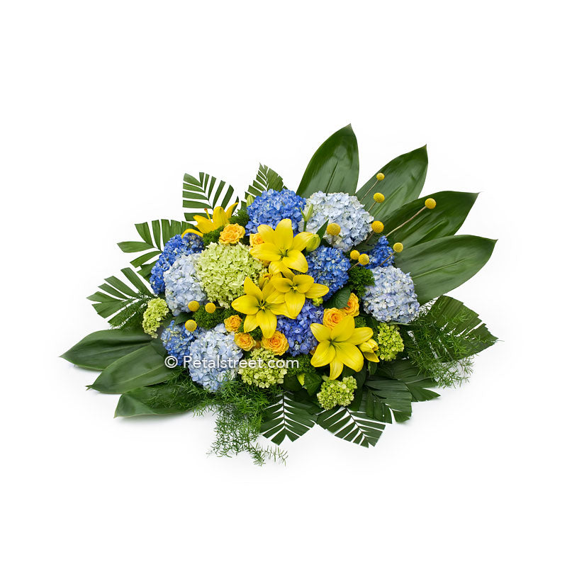Modern floral designed casket spray with yellow Lilies, large blue and green Hydrangea, and lush green Ti Leaves.