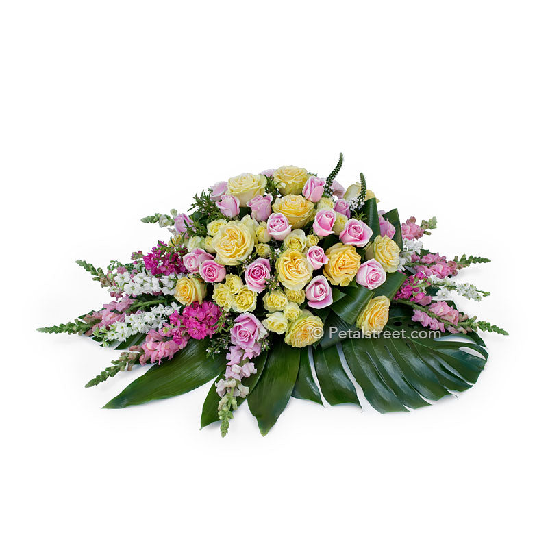 Beautiful artisan styled casket spray with pink and yellow Roses, Snapdragons, and large Monstera leaves.