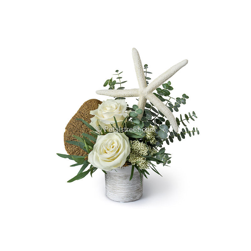 White Roses and Eucalyptus arranged in a white vase with a large dried starfish for a nautical beach themed flower arrangement