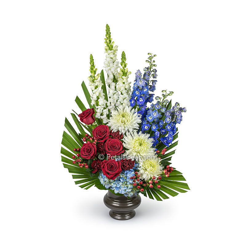 Red, white, and blue funeral basket has Roses, Snap Dragons, Delphinium, Mums, Hydrangea, Carnations, and custom hand-cut foliage.