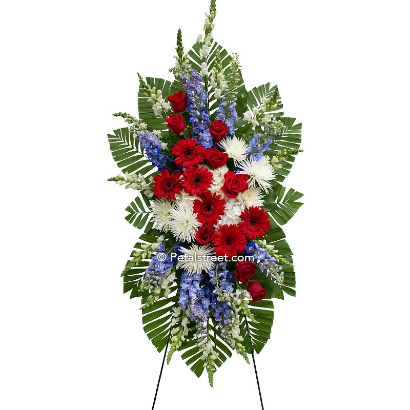 Red, white, and blue patriotic funeral spray featuring red Gerbera Daisies, white Spider Mums, and blue Delphinium.