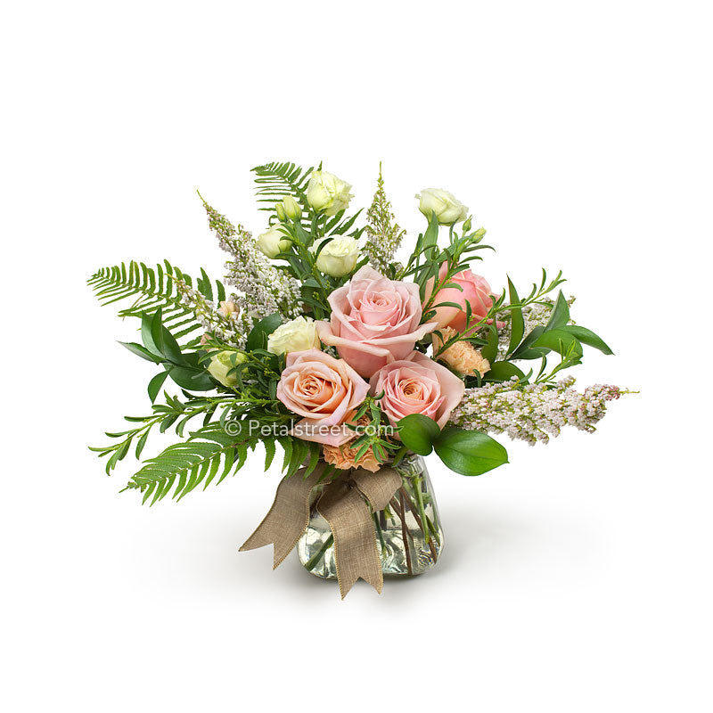 I mixed bouquet of Roses, Lisianthks, and other assorted flowers hand gathered and arranged in a vase.
