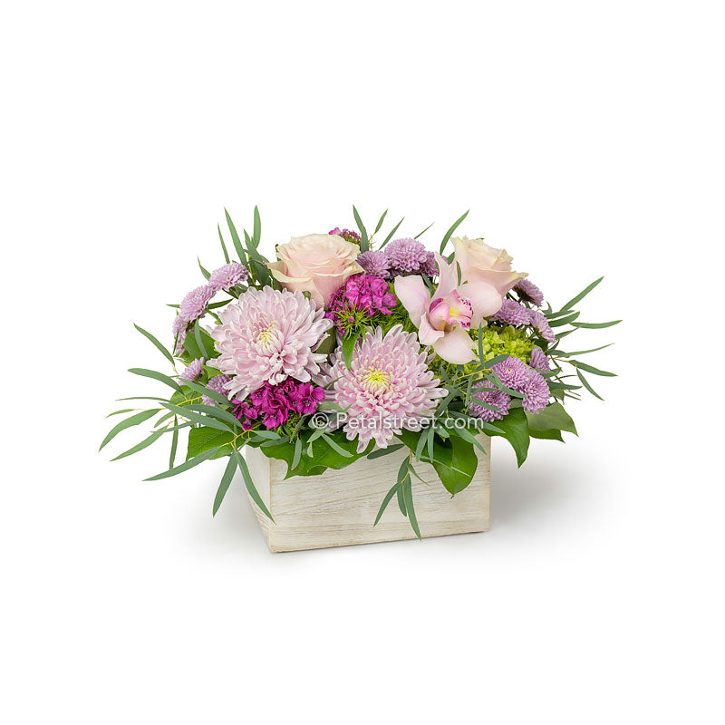 Mixed pink flowers arranged in a white wood box such as Roses, Orchids, Sweet William, Mums, and Eucalyptus