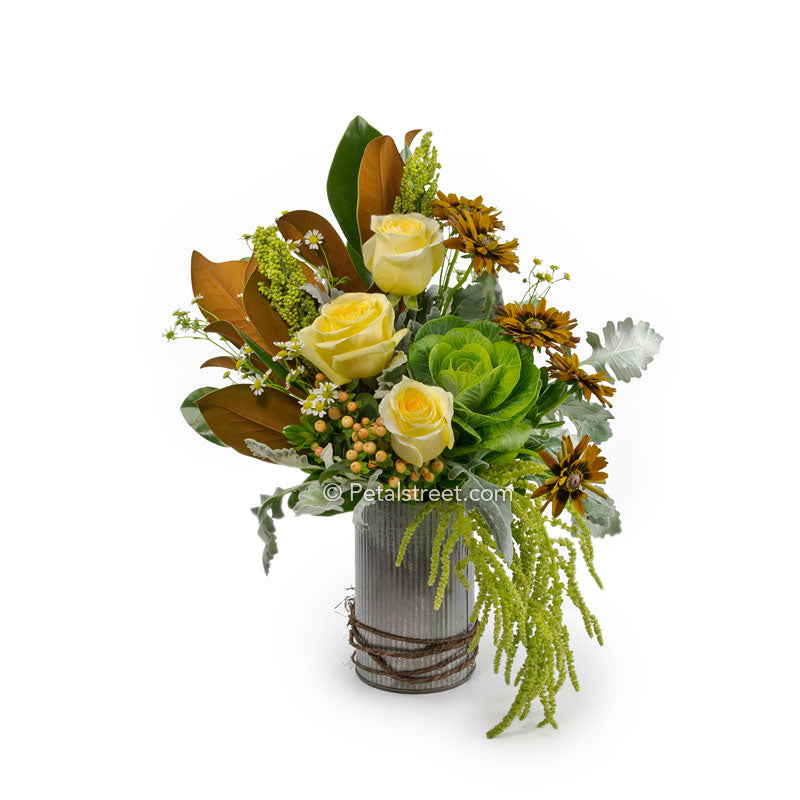 Rustic cylinder tin with bright yellow Roses, Kale, brown Mums, Berries, and Magnolia leaves for the Autumn season.