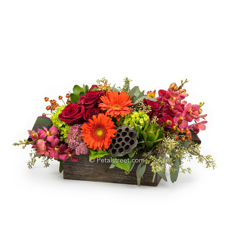 Rustic Fall Flower arrangement with red Roses, orange Gerbera Daisies, red Orchids, green mini Hydrangea, orange Alstroemeria, and Eucalyptus arranged in a box.