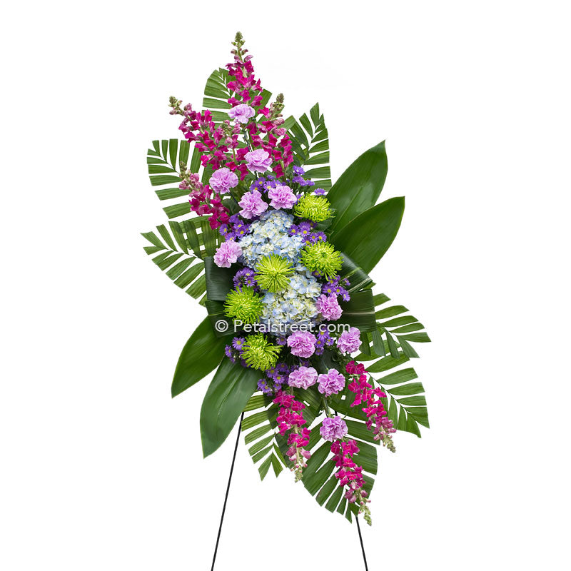 Funeral standing spray with pink, lavender, and blue mixed assortment of flowers by Petal Street Flower Company florist.