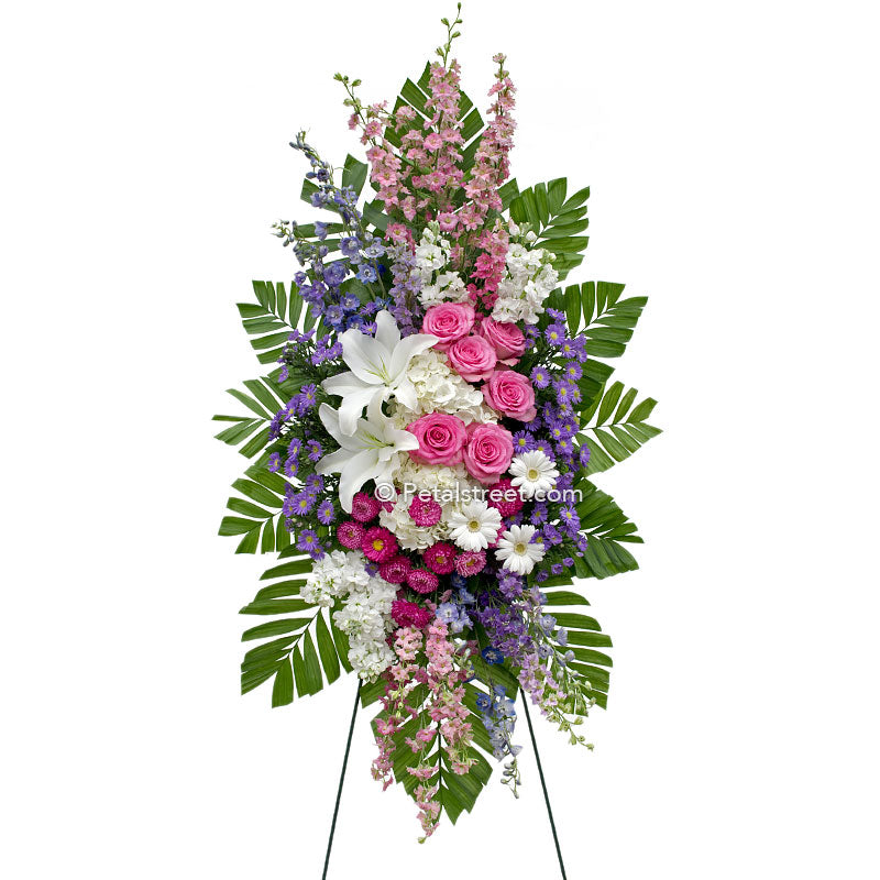 Standing spray with white Lilies and pink Roses, accent florals, lush Palm leaves.