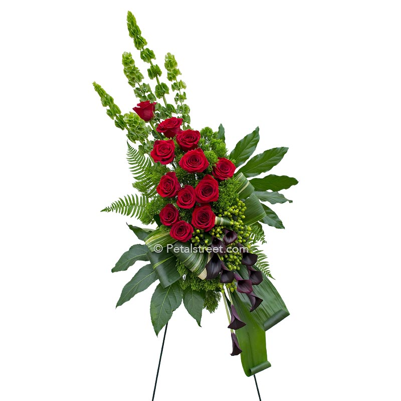Red Roses and deep plum Calla Lilies arranged with tropical leaves in this standing spray for funeral viewings.