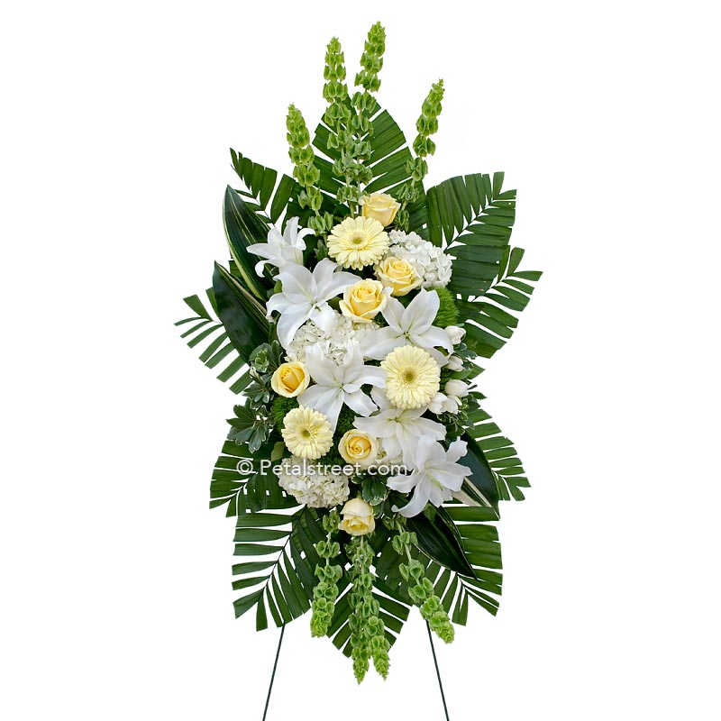 Soft yellow and white funeral standing spray with Lilies and Gerbera Daisies.