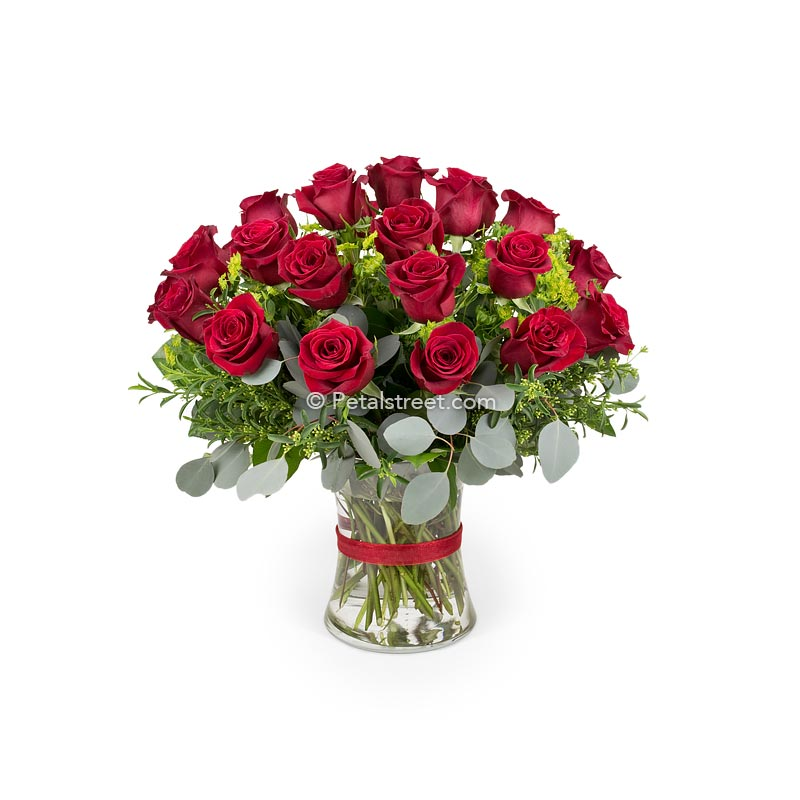 A classic sympathy vase of two dozen red Roses with Eucalyptus and Bupleurum accents.