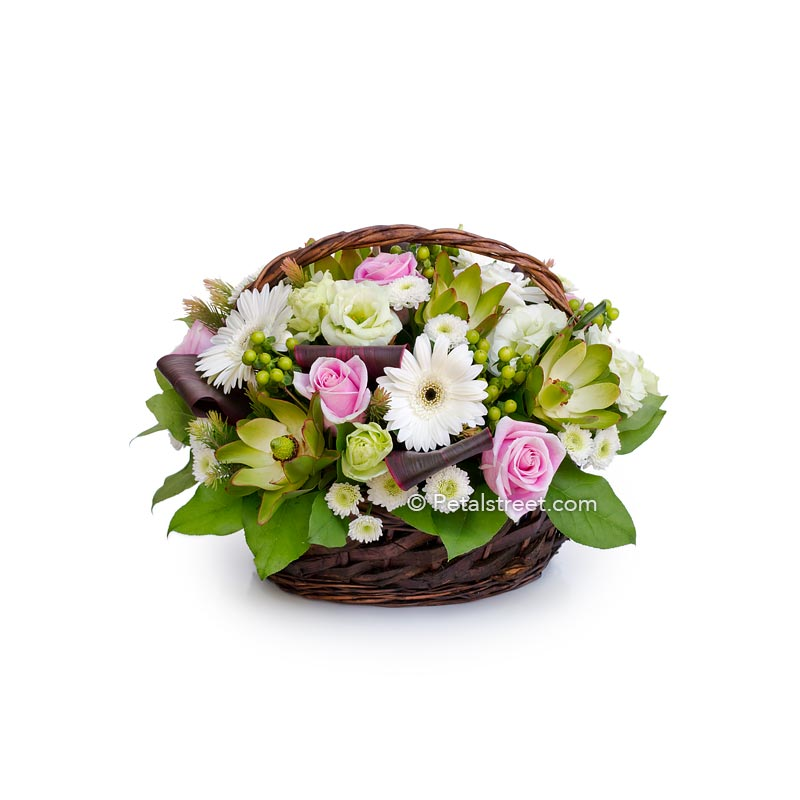 Flower sympathy basket with white Daisies, pink Roses, Lisianthus, Hypericum Berries, and Leucadendron.