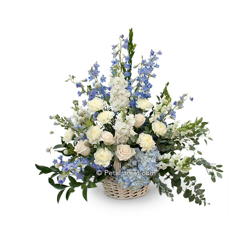 Sympathy basket of white Roses, Carnations, blue Hydrangea, blue Delphinium, Eucalyptus, and accent greenery.