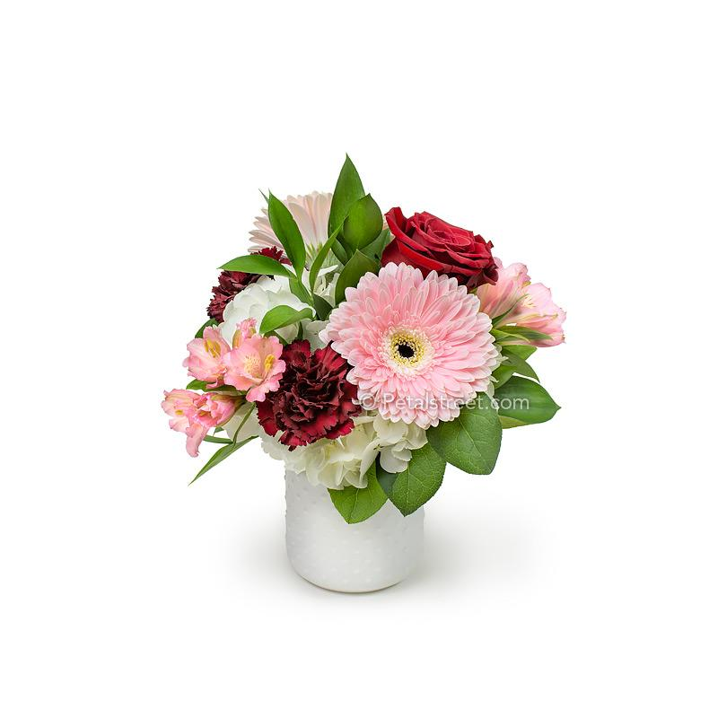 Valentine's Day flowers by Point Pleasant Florist Petal Street Flower Company has pink Gerber Daisies and Alstroemeria, red Roses and Carnations, white Hydrangea, and accent foliage arranged in a white hobnail jar. Classy and charming.