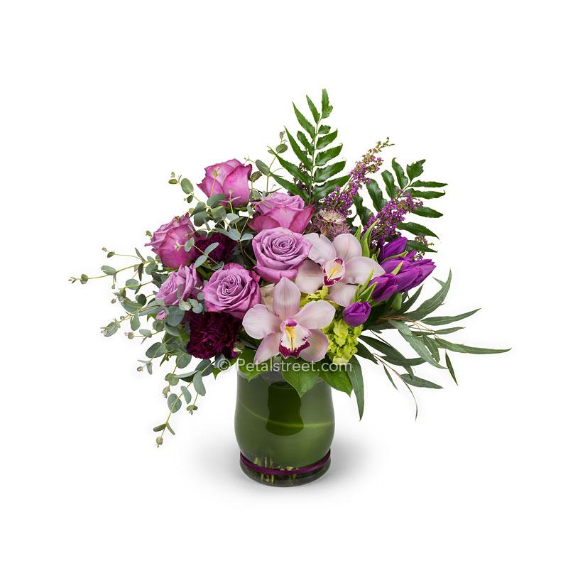 Mixed flowers in a vase for Valentine's Day delivery with purple Roses, purple Tulips, plum Carnations, pink Orchids, green Hydrangea,  and Eucalyptus.