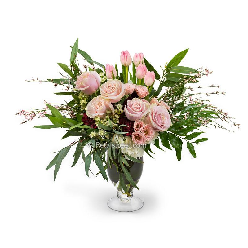 A tall vase of flowers with pink Roses, Lisianthks and Tulips, burgundy Carnations, Astrantia, Hydrangea, Eucalyptus, and mixed greenery accents.