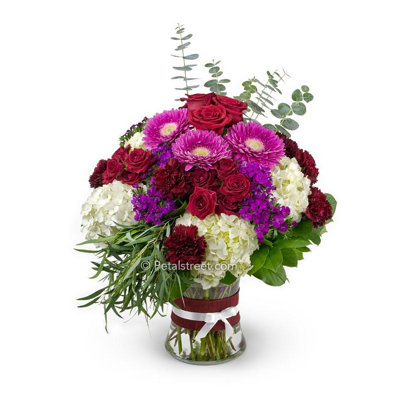 Large bouquet of flowers in a vase with red Roses, pink Gerbera Daisies, burgundy Carnations, pink Sweet William, white Hydrangea, and Eucalyptus foliage.